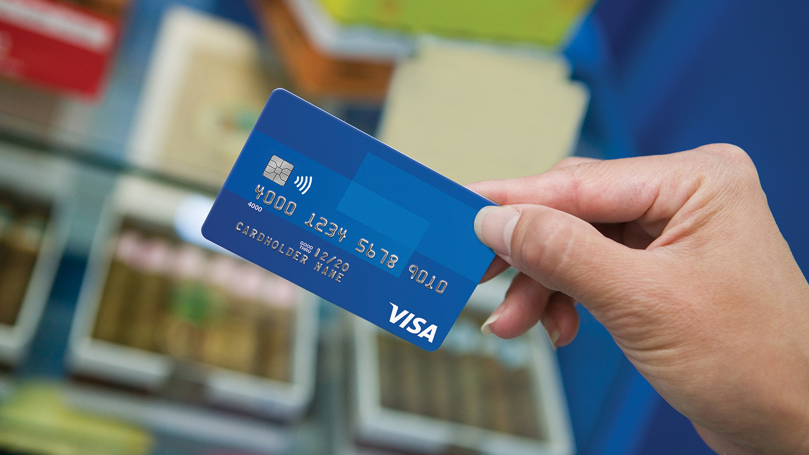 A close-up of a hand holding a Visa card.